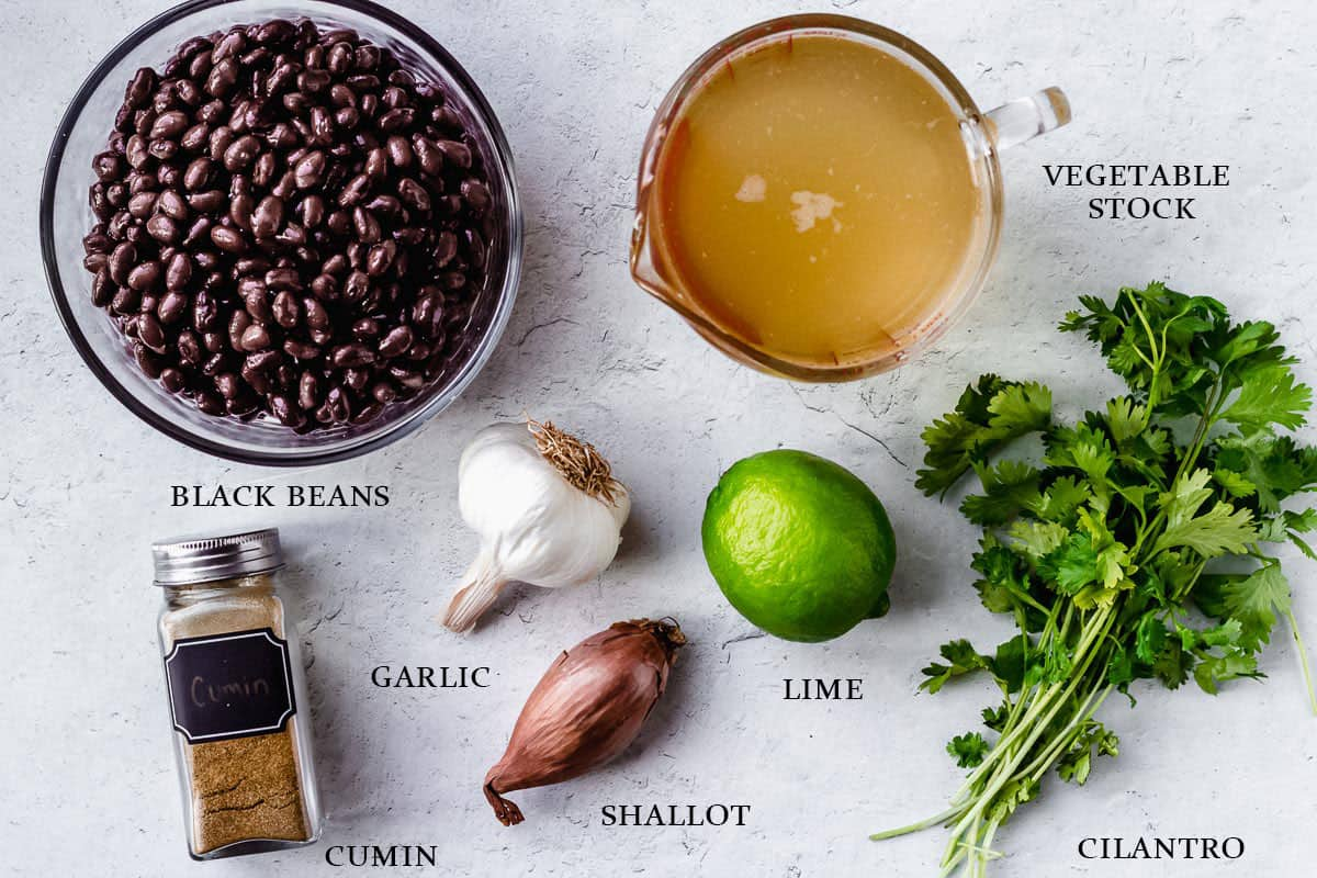 Ingredients to make black bean and lime soup on a white background with labels