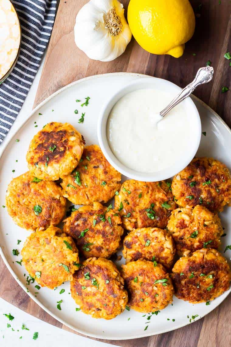 Overhead of Lemon Garlic Salmon Cakes on a round white plate with a smaller white bowl of aioli and a lemon, garlic bulb, blue and white towel and wood board in the background