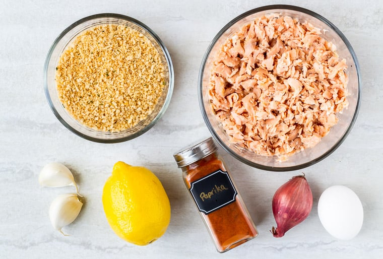 Ingredients needs to make lemon garlic salmon cakes in glass bowls on a white background