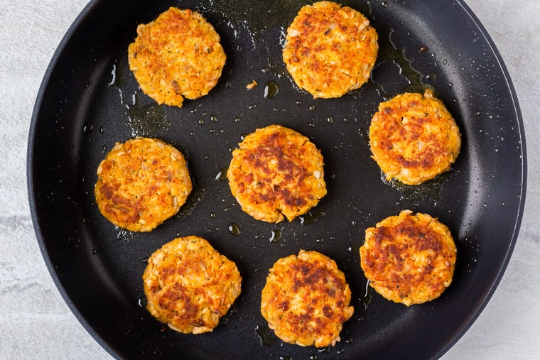 8 salmon cakes cooking in a black skillet over a white background