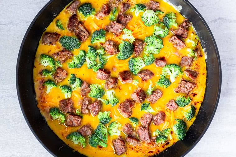 scrambled eggs topped with sausage, broccoli and cheese in a black skillet over a white background