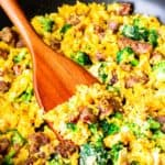close up of scrambled eggs with sausage, cheese, and broccoli in a black skillet with a wood turner lifting some up