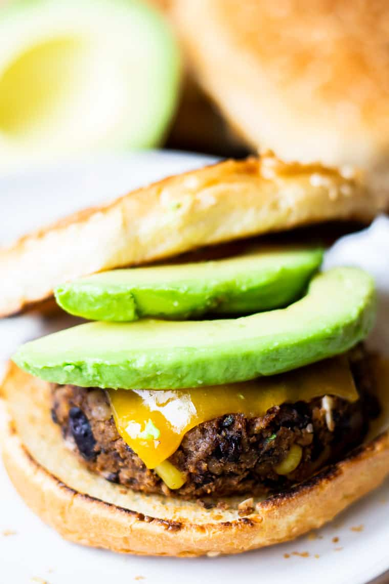 A southwestern black bean burger on a toasted bun with melted cheese and avocado with half an avocado and a bun blurred in the background