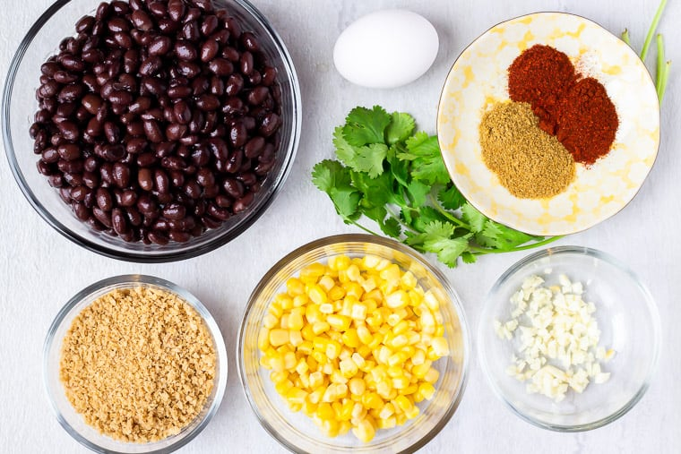 The ingredients needed to make Southwestern Black Bean Burgers in glass bowls on a white background