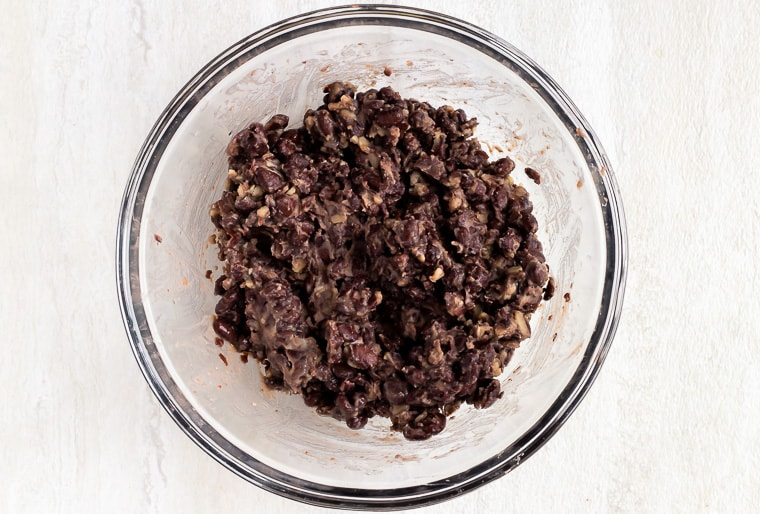 Mashed black beans in a glass bowl over a white background