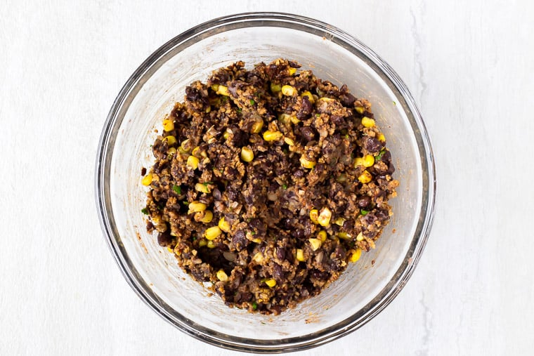 Mashed black beans, corn, and spices in a glass bowl over a white background