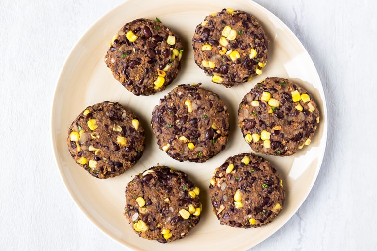7 black bean burger patties on a tan plate over a white background