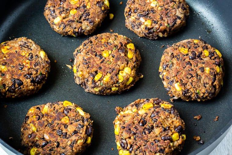 7 black bean burger patties cooking in a black skillet