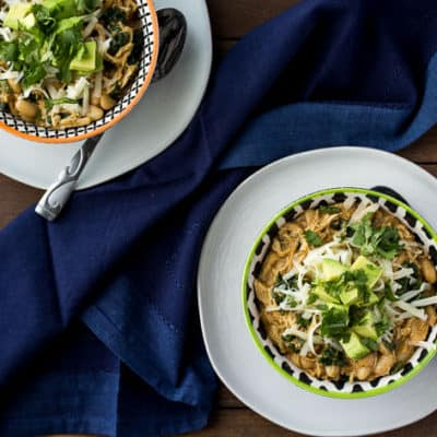 Two Bowls of Spicy White Turkey Chili Topped with Cheese, Avocado, and Cilantro