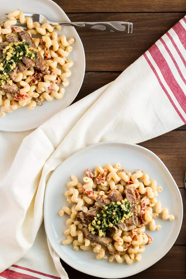 2 bowls of pasta topped with Tuscan steak, pine nuts and fresh basil over a wood background with a red and cream color napkin