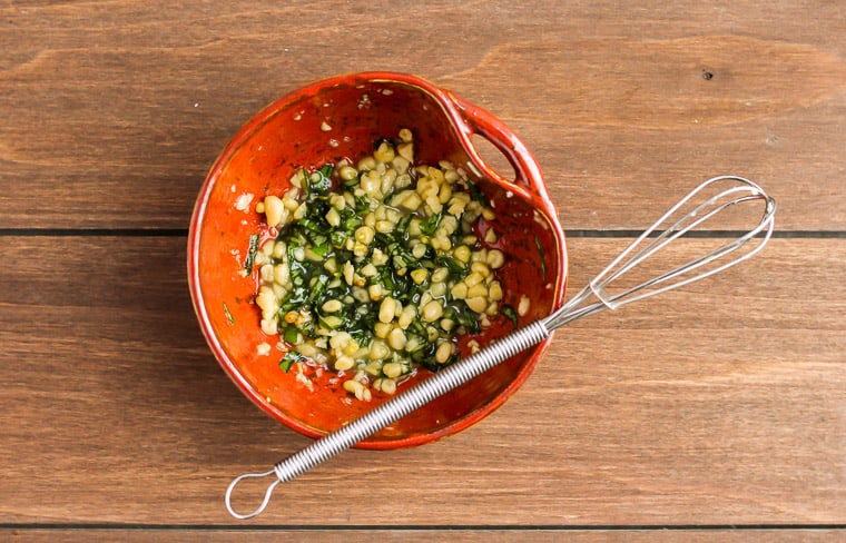 Pine nut and basil topping in a small orange bowl with a mini whisk over a wood background