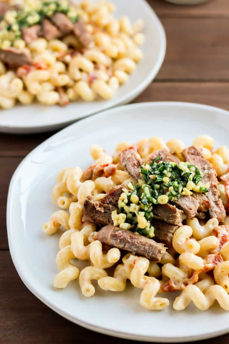 A gray plate with Tuscan steak and pasta with a second plate in the background on a wood background