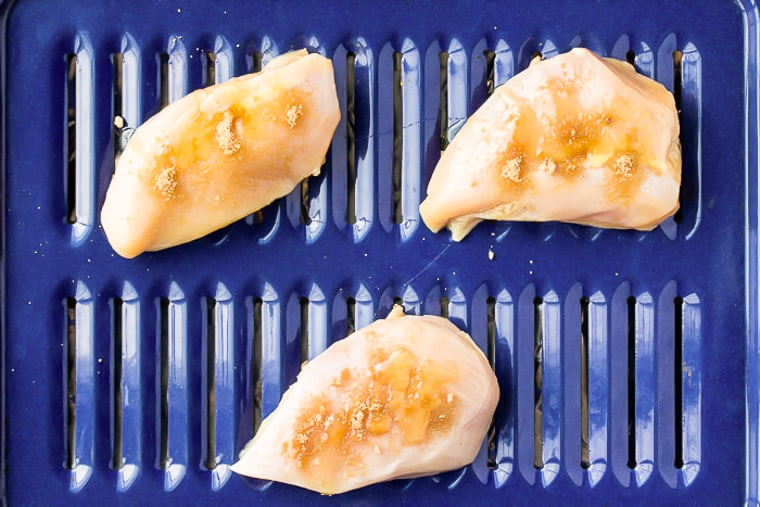3 Chicken breasts on a blue broiler pan sprinkled with honey and brown sugar