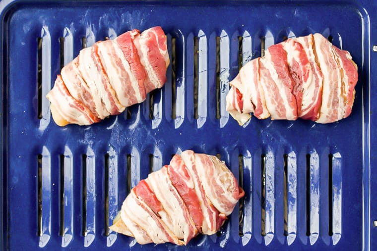 2 chicken breasts wrapped in bacon on a blue broiler pan