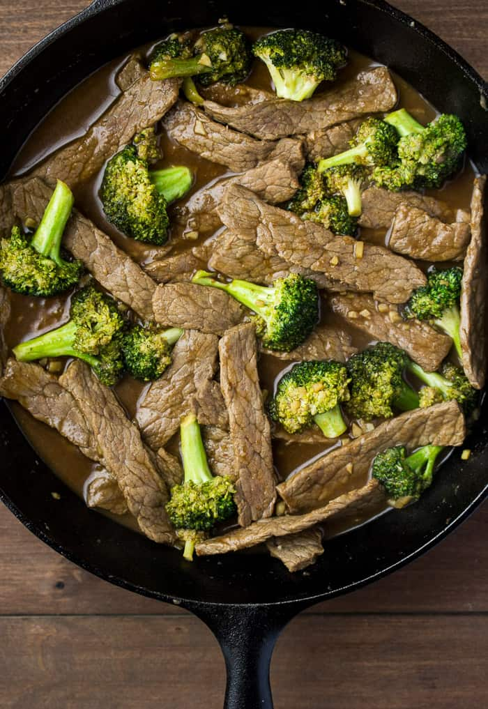 Beef and Broccoli Cooking in a black skillet over a wood background