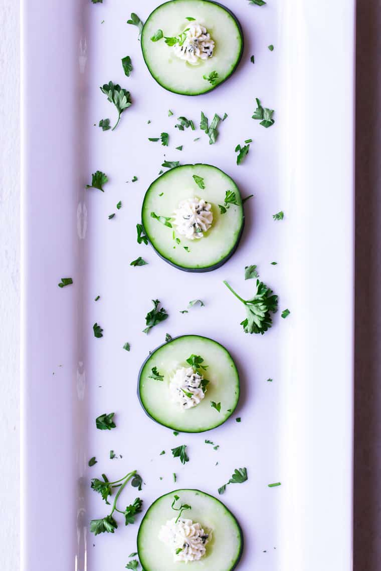 a rectangular white tray with 4 cucumber bites with herb cream cheese and extta herbs spread around