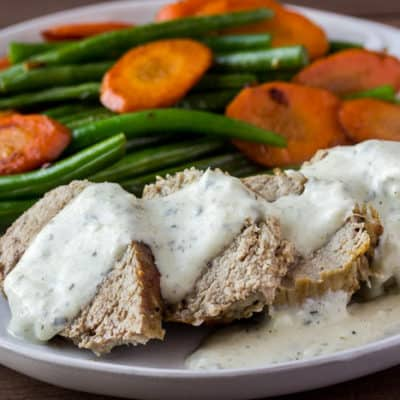 Home Chef Pork Tenderloin with Basil-Pecorino Sauce on a White Plate