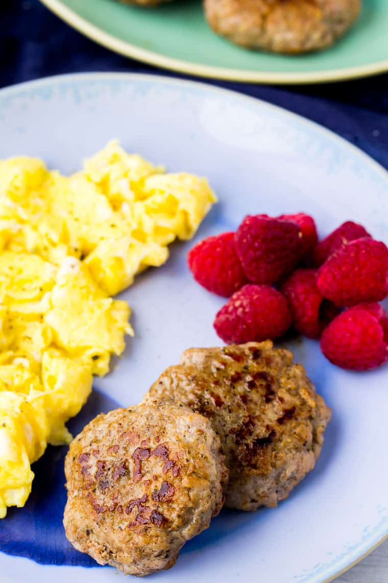 2 Homemade Breakfast Sausage patties on a blue plate with scrambled eggs and raspberries with a second green plate with sausage on it on the background and a blue napkin