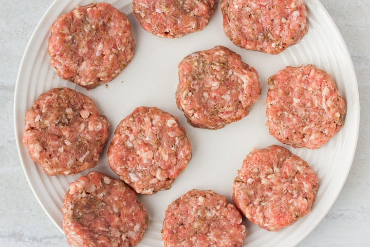 10 Sausage patties on a white plate before cooking