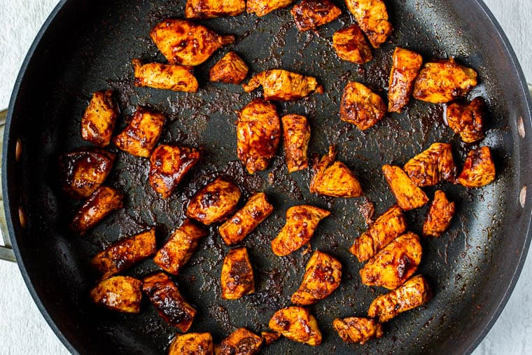 Seasoned chicken cubes cooking in a black skillet