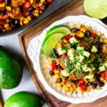 Overhead of A white bowl filled with quinoa, chicken, black beans, corn, red pepper, avocado, and lime slices on a wood board with 2 lime halves, and part of a skillet in the background
