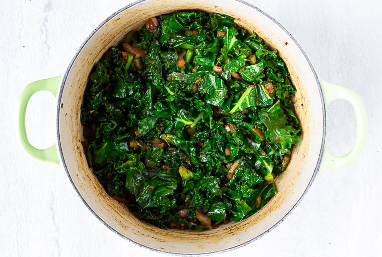 Kale and vegetables cooking in a Dutch oven over a white background