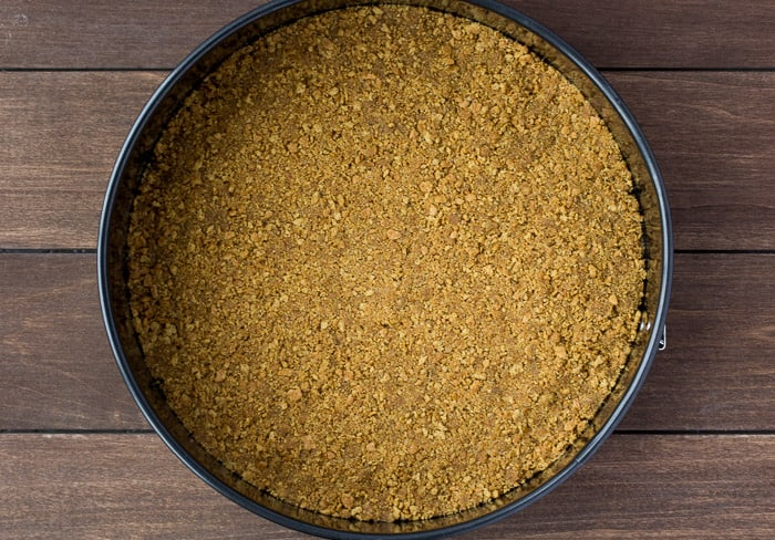 Graham Cracker Crust in a spring form pan over a wood background