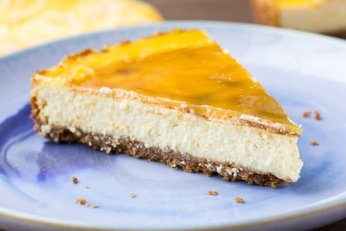 A Slice of Vanilla Orange Cheesecake with Orange Glaze on a blue plate
