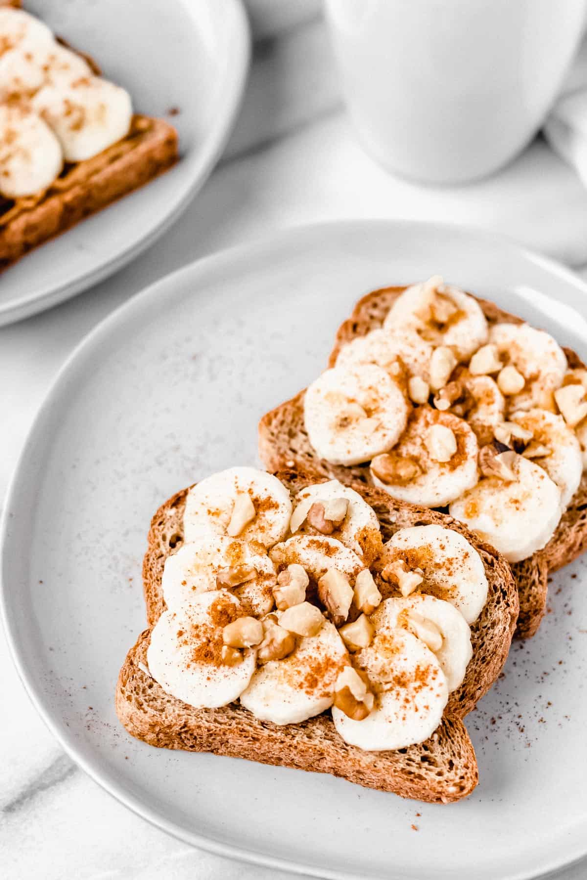 2 slices of Banana Nut Bread Toast on a white plate with a second plate and white mug in the background