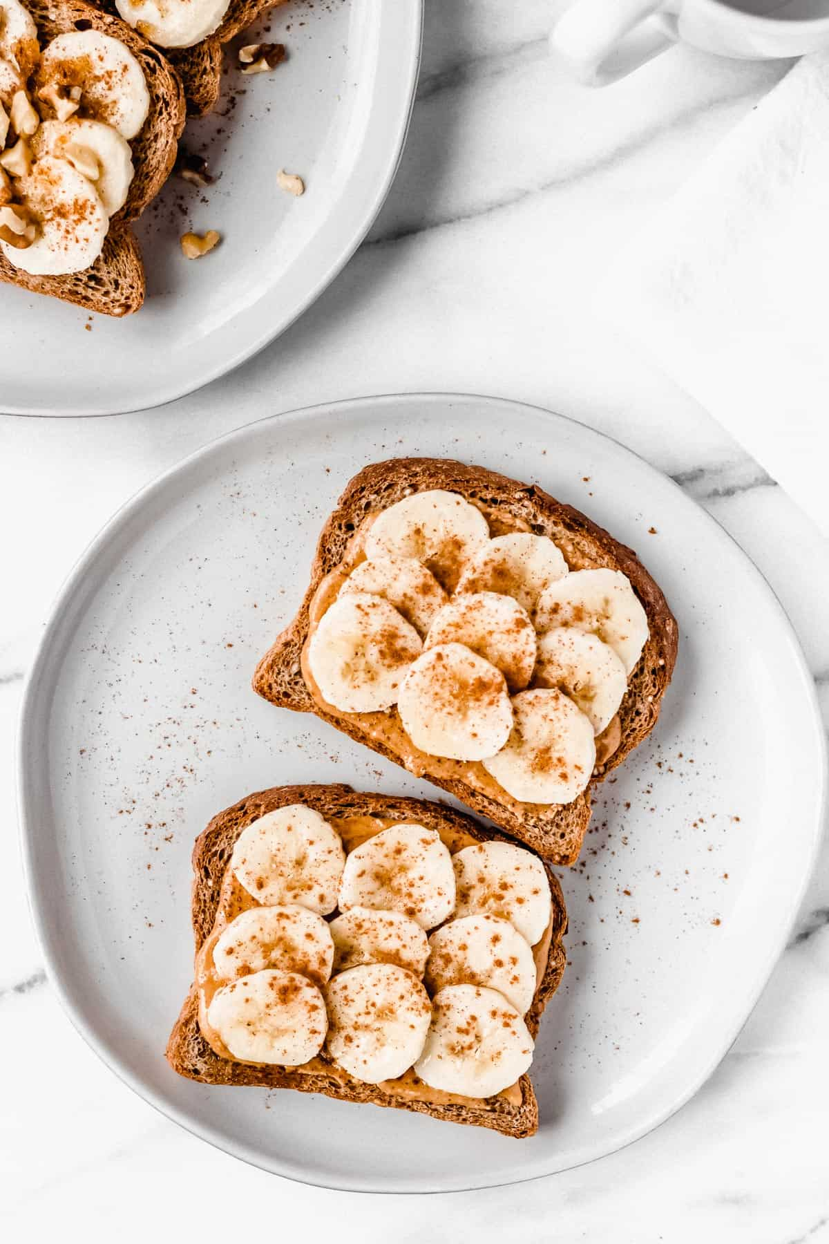 Overhead of banana toast with peanut butter, cinnamon and honey on a white plate
