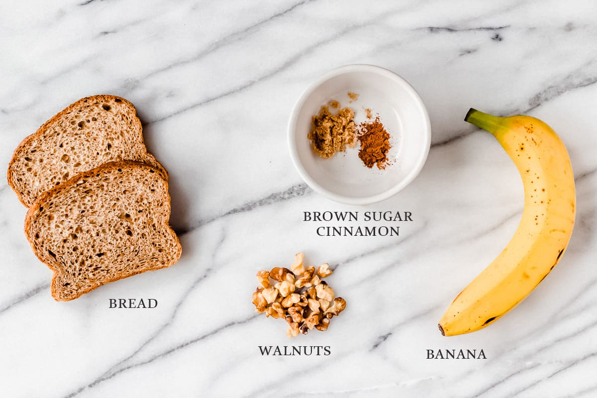 Ingredients to make banana nut bread banana toast on a marble background with labels