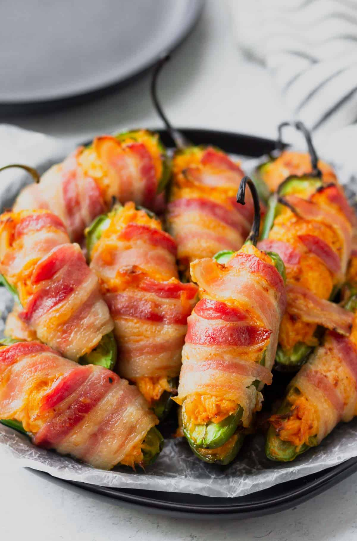 Buffalo Chicken Jalapeno Poppers wrapped in bacon on a black plate with a second plate in the background