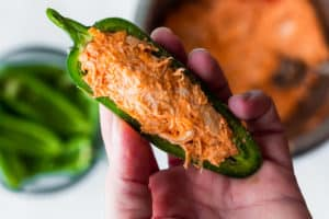 Half of a jalapeno pepper stuffed with Buffalo chicken