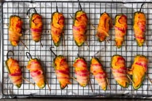 Cooked bacon wrapped buffalo chicken jalapeno poppers on a rack