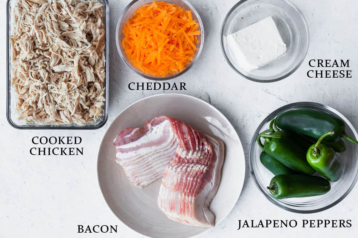 Ingredients for buffalo chicken jalapeno poppers on a white background with labels