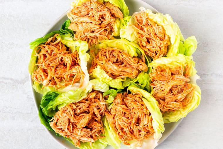 7 Buffalo chicken filled lettuce cups on a white plate over a white background