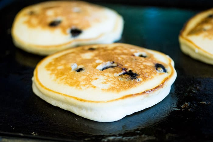 Fluffy Blueberry Pancakes Cooking on a Griddle