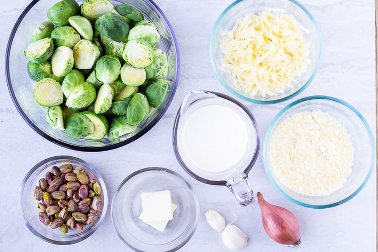 Ingredients needed to make Brussels Sprouts Gratin in glass bowls over a white background