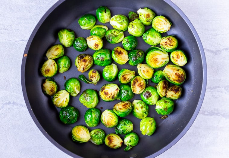 Brussels sprouts cooking in a black skillet over a white background