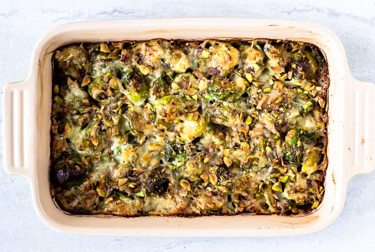 Baked Brussels Sprouts Gratin in a rectangular baking dish over a white background
