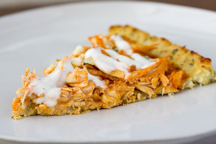 A Slice of Buffalo Chicken Pizza Topped with Ranch Dressing on a white plate close up