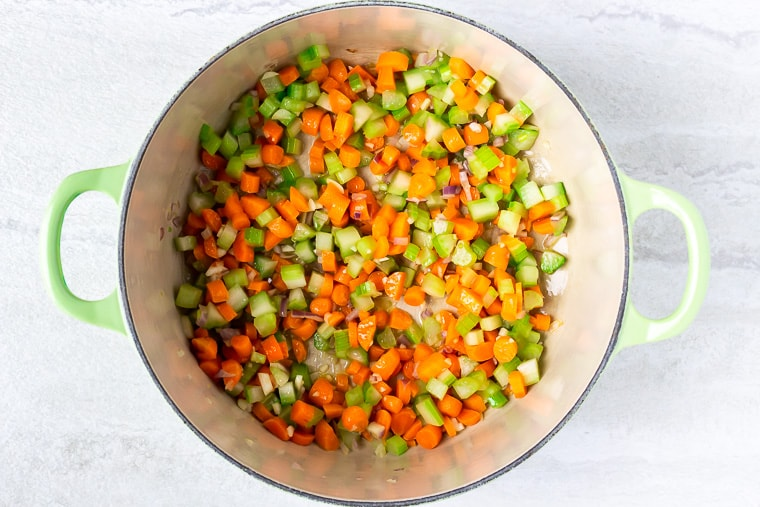 Carrots, celery, garlic, and shallots cooking in a light gree dutch oven over a white background