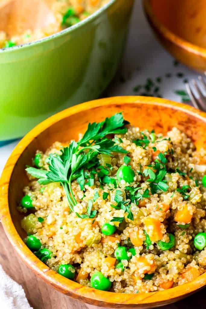Quinoa Pilaf in an orange wood bowl on a wood board with a green dutch oven and a second orange wood bowl in the background