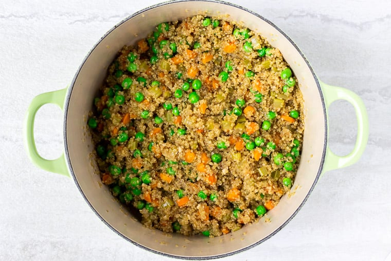 Quinoa, carrots and peas in a light green dutch oven over a white background