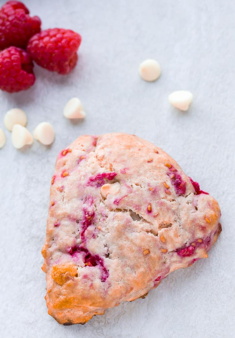 A single White Chocolate Raspberry Scone with extra white chocolate chips and 3 fresh raspberries in the background on a white backdrop