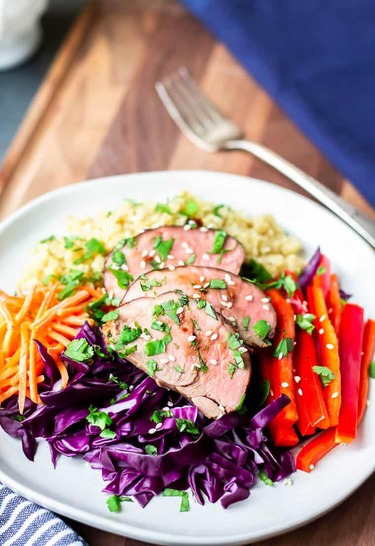 Asian Pork Salad on a white plate with a fork and dark blue napkin in the background on a wood board