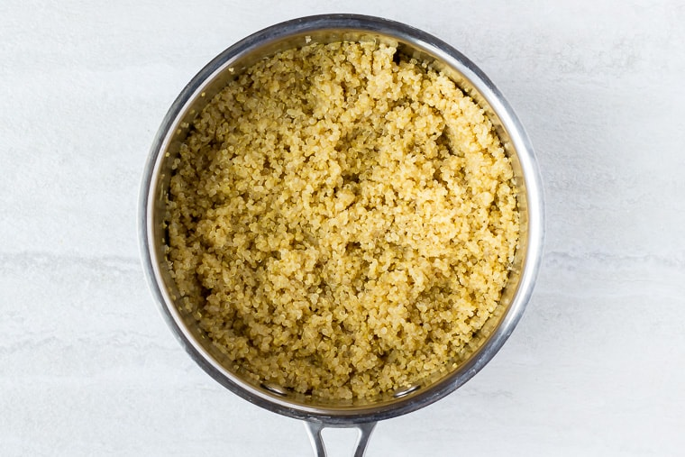 Cooked quinoa in a silver pot over a white background