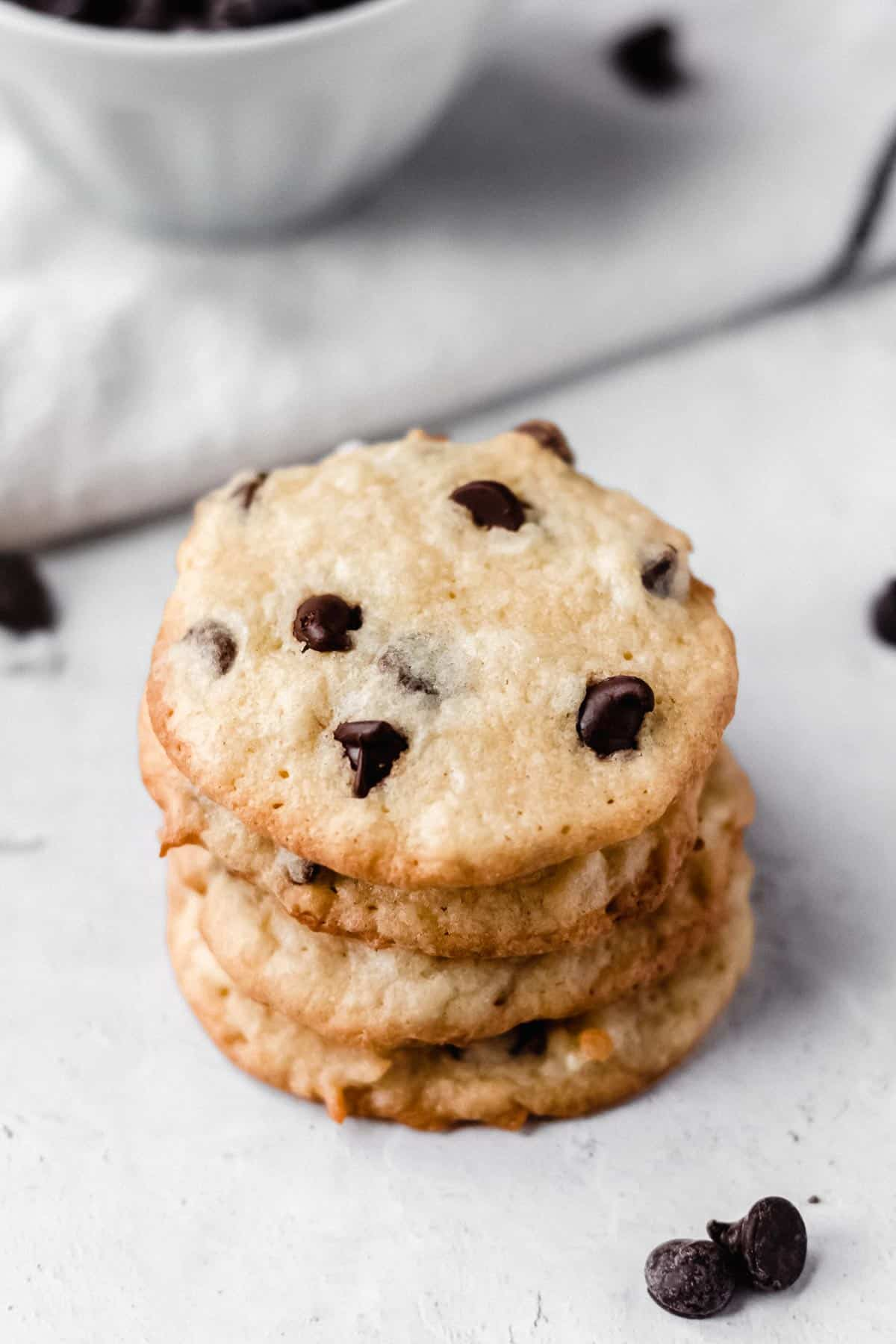 Stack of 5 coconut chocolate chip cookies on a white background with chocolate chips, a white towel and a bowl in the background