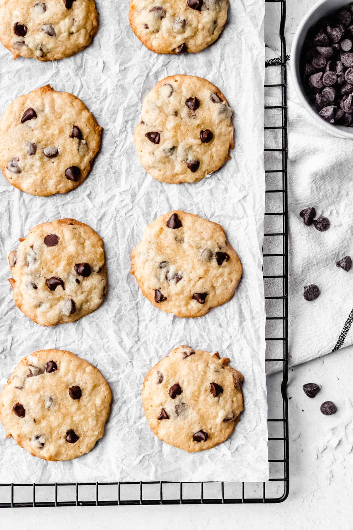Coconut chocolate chip cookies on a cooking rack and parchment paper with chocolate chips on the side