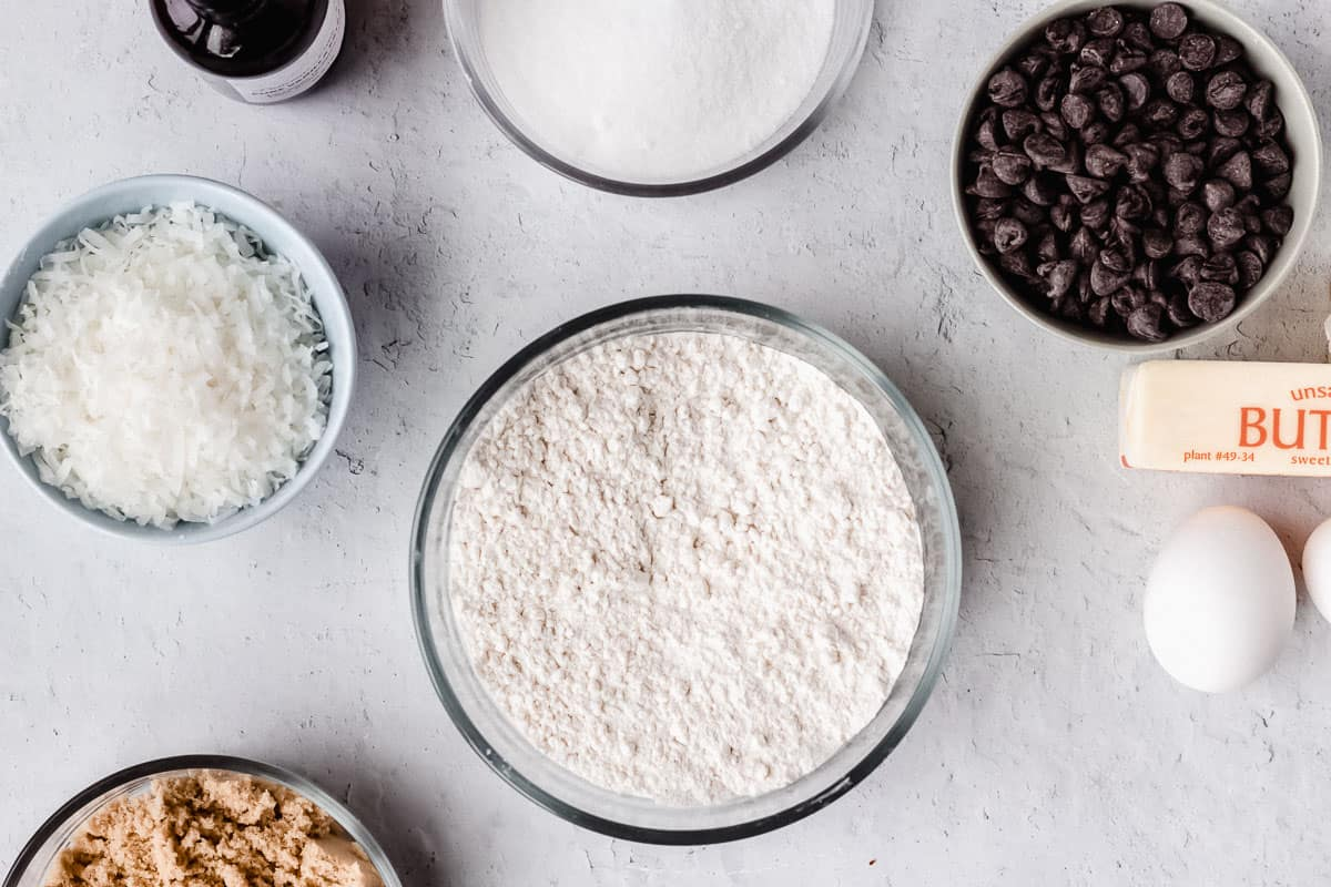 Dry ingredients for chocolate chip cookies in a bowl with other ingredients around it